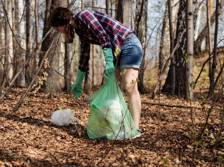 Dobrovolnice při úklidu odpadu v lese